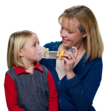 Dziecko używa przy pomocy swojej matki, AeroChamber z maską